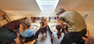 Drehen auf der Scheibe: Erwachsene zeigen Kindern wie das Drehen geht. ch-keramik.ch